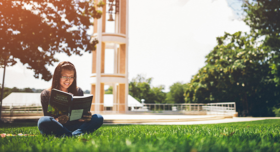 Student reading book on bell tower quad
